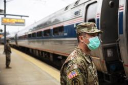 Members of the Rhode Island National Guard look for passengers getting off from a train from New York as it arrives Saturday, March 28, 2020, in Westerly, R.I.