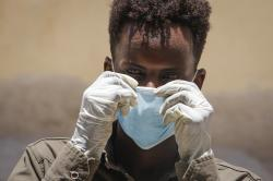 A Somali man wears a surgical mask and gloves on the street after after the government announced the closure of schools and universities and banned large gatherings,