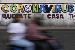 """In this April 28, 2020 photo, a couple rides a motorcycle past a painted sign reading in Spanish """"Coronavirus. Stay Home,"""" in Iztapalapa, Mexico City"""