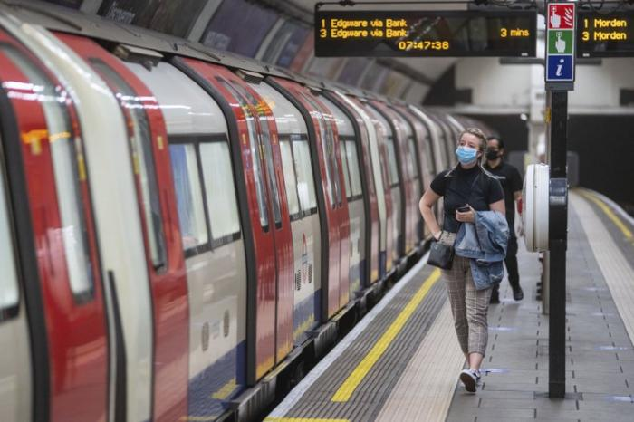 A commuter wearing a protective face mask walks along the platform at Clapham Common underground station, London, as train services increase this week as part of the easing of coronavirus lockdown restrictions, Thursday May 21, 2020