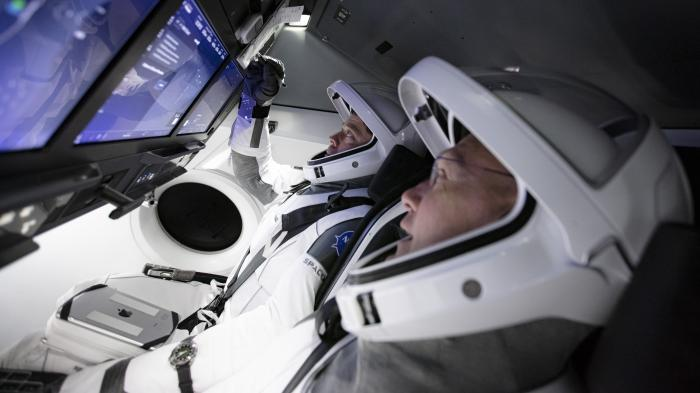 In this Thursday, March 19, 2020 photo made available by SpaceX, astronauts Doug Hurley, foreground, and Bob Behnken work in SpaceX's flight simulator at the Kennedy Space Center in Cape Canaveral, Fla.