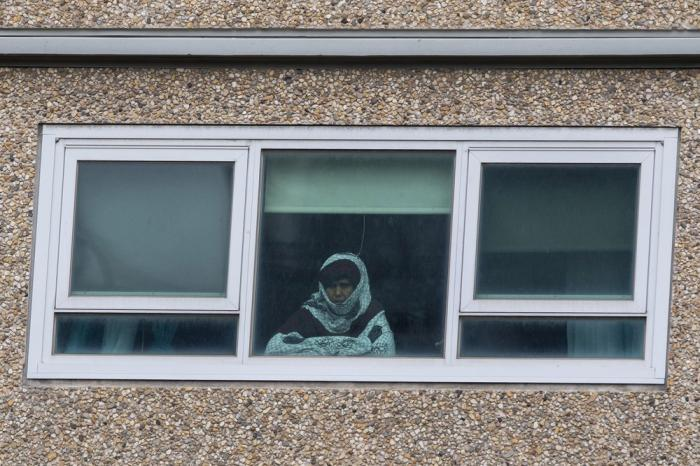 A woman looks out a window from a locked-down public housing tower in Melbourne, Monday, July 6, 2020