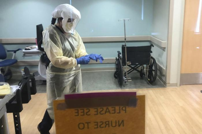 In this photo provided by the UPMC, Dr. Ruba Nicola, chairwoman of family medicine at UPMC East, adjusts her personal protective equipment at the UPMC East hospital in Monroeville, Pa., on April 17, 2020