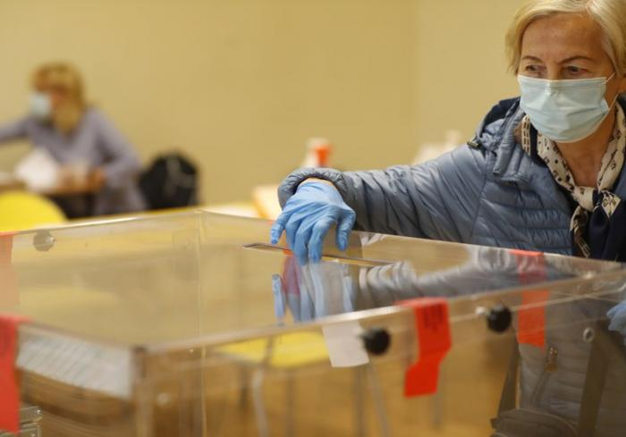 A woman casts her vote during presidential runoff election in Krakow, Poland, Sunday, July 12, 2020