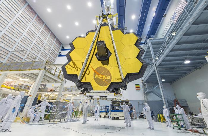 In this 2017 photo made available by NASA, technicians lift the mirror assembly of the James Webb Space Telescope using a crane inside a clean room at NASA's Goddard Space Flight Center in Greenbelt, Md.