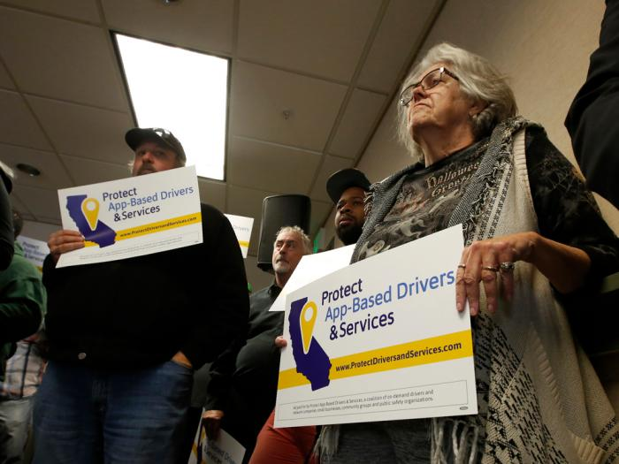 In this Oct. 29, 2019, file photo, Carla Shrive, right, who drives for various gig companies, joined other drivers to support a proposed ballot initiative challenging a recently signed law that makes it harder for companies to label workers as independent contractors, in Sacramento, Calif.