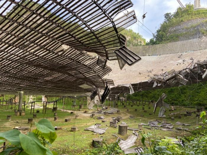 In this Tuesday, Aug. 11, 2020 file photo, provided by the Arecibo Observatory, shows the damage done by a broken cable that supported a metal platform, creating a 100-foot (30-meter) gash to the radio telescope's reflector dish in Arecibo, Puerto Rico