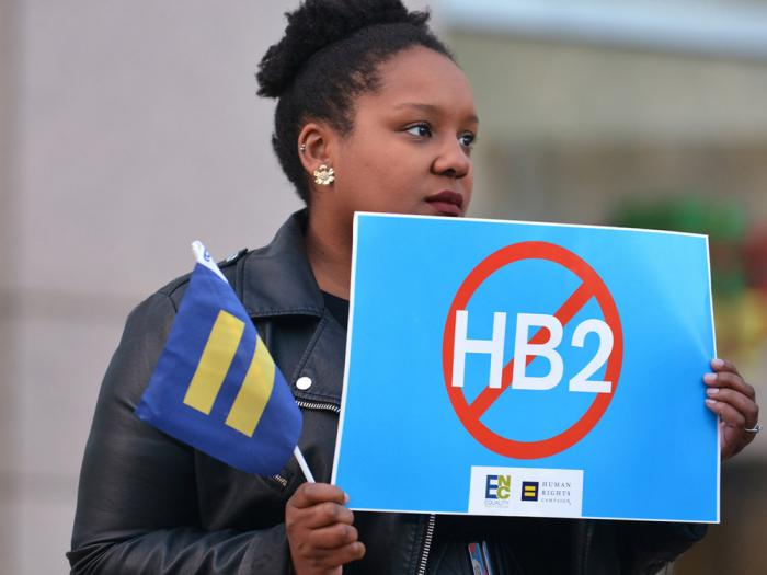 Cassandra Thomas of Human Rights Campaign holds a sign advocating the repeal of HB2 on Dec. 7, 2016, in Charlotte