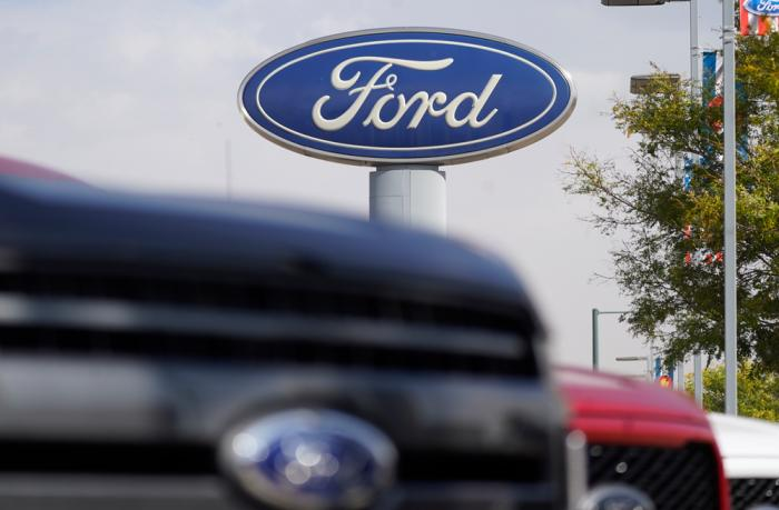 In this Sunday, Oct. 11, 2020, file photo, the company logo hangs over a row of 2020 F-150 pickup trucks at a Ford dealership, in Denver