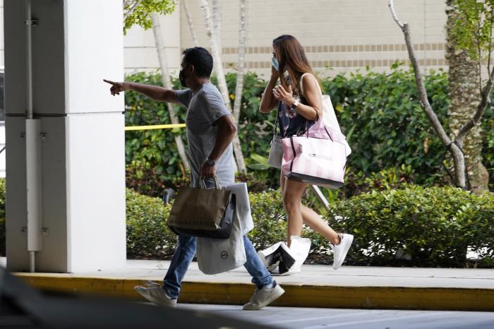 Shoppers walk towards a garage after leaving the Aventura Mall where a shooting left three people injured and several suspects in custody, Saturday, May 8, 2021, in Aventura, Fla.