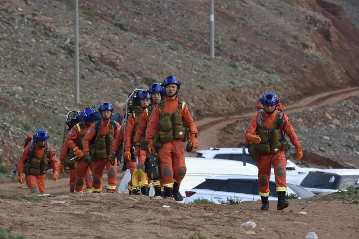 In this photo provided by China's Xinhua News Agency, rescuers walk into the accident site to search for survivors in Jingtai County of Baiyin City, northwest China's Gansu Province, Sunday, May 23, 2021.