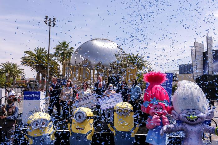California Governor Gavin Newsom, center, celebrates with other guests after the Vax for the Win lottery contest during a news conference at Universal Studios in Universal City.