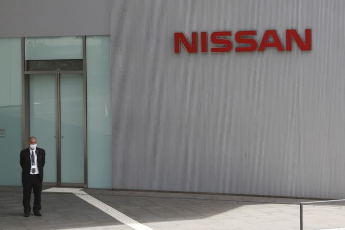 A man stands at Nissan Motor Co.'s global headquarters in Yokohama, near Tokyo, Tuesday, June 22, 2021