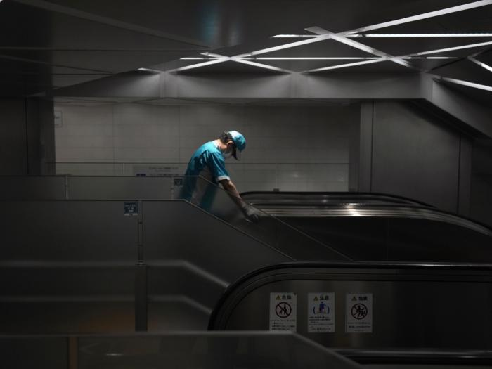 An employee wearing a protective mask to help curb the spread of the coronavirus cleans the handrail of an escalator at the underneath of a subway station Thursday, July 29, 2021, in Tokyo