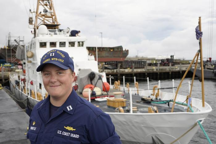 U.S. Coast Guard Lt. Kelli Normoyle, Commanding Officer of the Coast Guard Cutter Sanibel, stands for a photograph near the vessel, Thursday, Sept. 16, 2021, at a shipyard in North Kingstown, R.I.